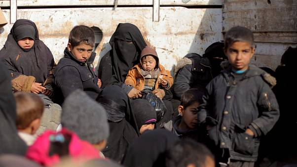 Women and children sit at a back of a bus near Baghouz, Deir Al Zor provinc
