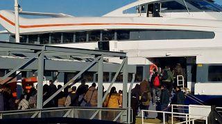 Passengers prepare to board a ferry