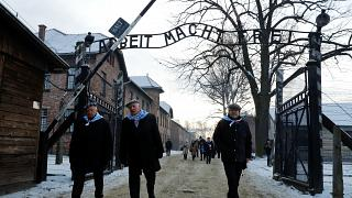 Holocaust survivors walking through the Auschwitz gates