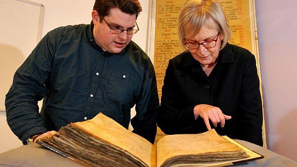 Archivist Gary Brannan and Professor Sarah Rees Jones look at the register