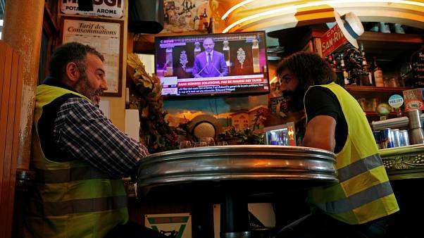 Christophe Chalencon (left) watching a televised speech by France's PM