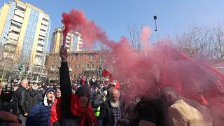 A protester holds a flare during an anti-government rally in Albania