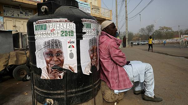 A man sits next to a campaign poster after Nigeria's elections are delayed.