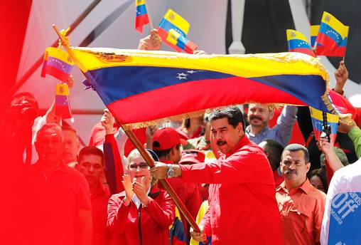 Maduro waves a Venezuelan flag