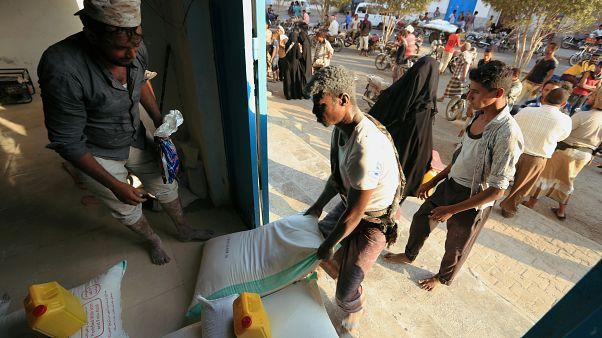 عامل يحمل كيسًا من الدقيق في مركز توزيع المساعدات للأمم المتحدة /اليمن