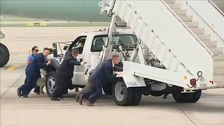 Bodyguards push the boarding steps out of the way for Air Force One