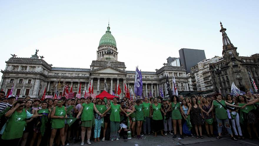 Activists hold hands outside the Argentine National Congress