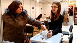 A woman casts her vote during advanced voting in Tallin