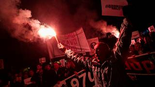 A demonstrator holds a flare during civic protest in Podgorica, Montenegro