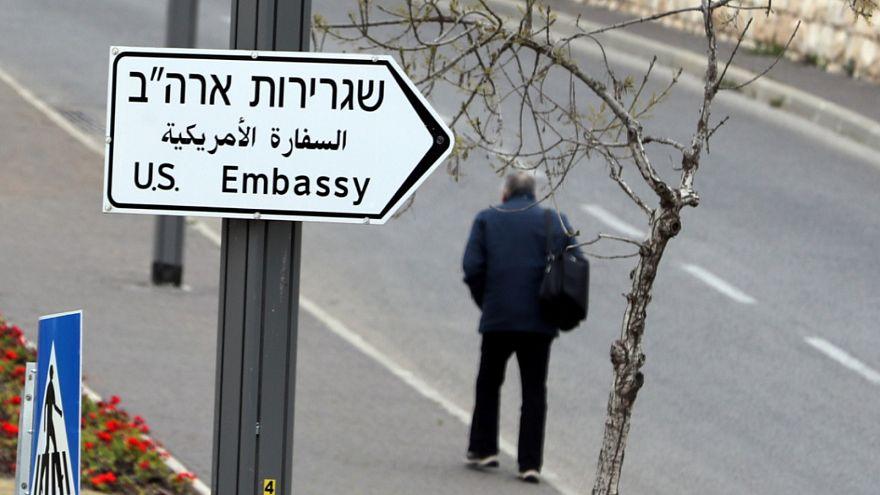 رجل يسير بجوار لافته تشير إلى اتجاه السفارة الإسرائيلية في القدس