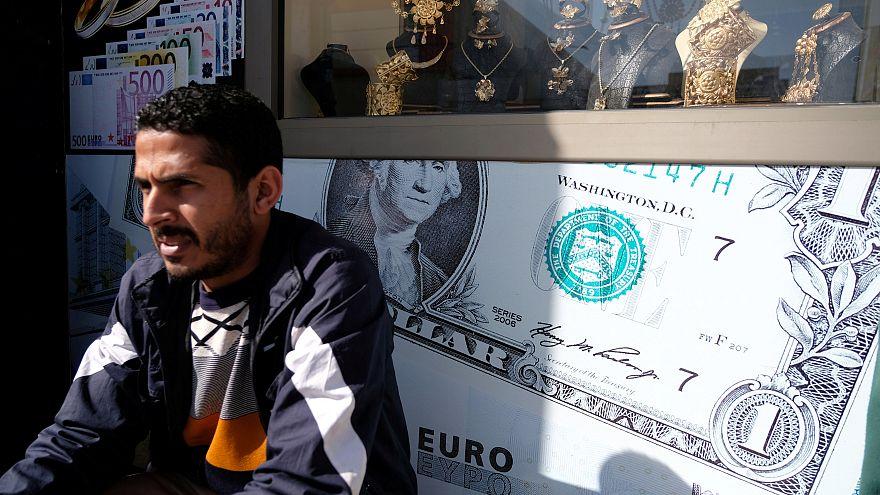 مواطن ليبي يجلس أمام مكتب للصرافة في بنغازي