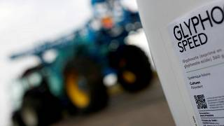 File picture: A can of glyphosate weedkiller is seen in front of a tractor