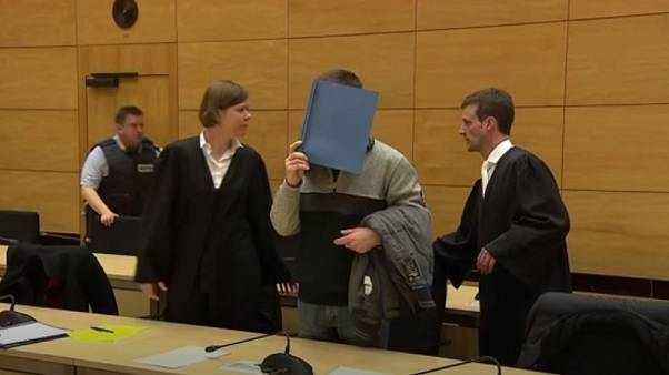 The defendant covered up his face in court with a folder