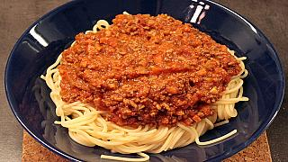 """A plate of """"spaghetti bolognese"""", spaghetti topped with a tomato meat sauce"""