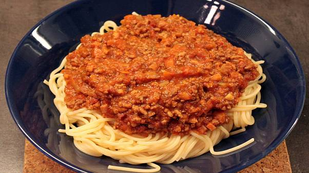 "A plate of ""spaghetti bolognese"", spaghetti topped with a tomato meat sauce"