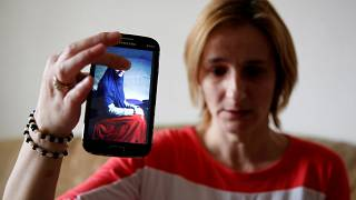 سيدة بوسنية تحمل هاتف محمول عليه صورة أختها في سوريا