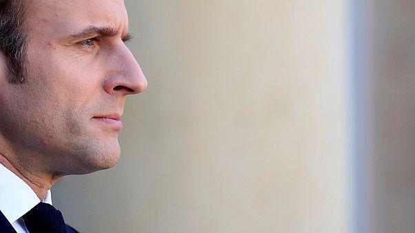 Emmanuel Macron watches as Angela Merkel leaves a meeting in Paris.