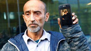 عمر نبي أمام محكمة كرايست تشيرش يحمل صورة والده الذي قضى في حادثة نيوزيلندا