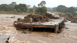 A man looks at a washed away bridge along Umvumvu river in Chimanimani