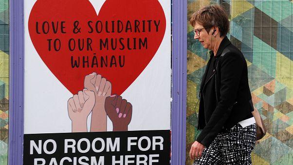 امرأة تمر بجانب منشور يدعم مسلمي نيوزيلندا بعد مذبحة المسجدين