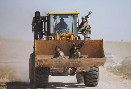 Fighters from SDF ride excavator in the village of Baghouz, Syria