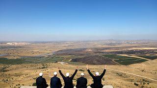 عدد من دروز الجولان المحتل يجلسون مقابل الشطر الشمالي داخل سوريا