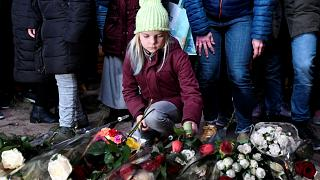 A girl lays flowers during a silent march in Utrecht to honour victim