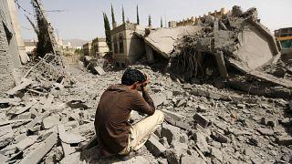 يمني يجلس على أنقاض منزل عسكري موال للحوثيين دمر إثر غارات جوية في صنعاء