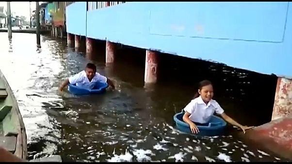 Peru'da sel basan bölgelerde çocuklar okula kovalarla gitti