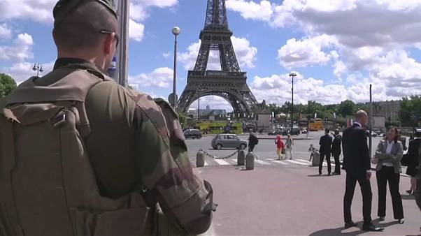 عسكري فرنسي يقف أمام برج إيفل وسط العاصمة باريس.