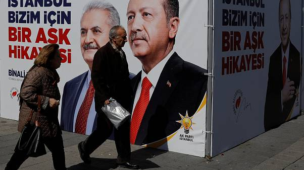 People walk past an AK Party campaign tent, Istanbul, March 2019