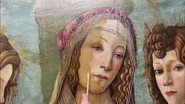 Art restorer working on a workshop version of Botticelli's painting
