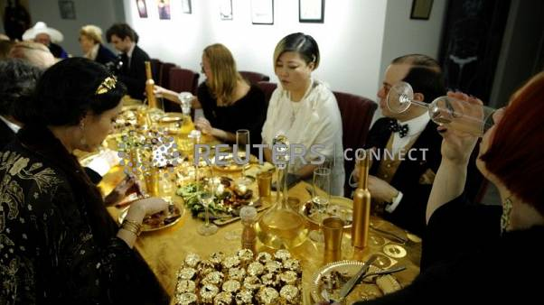 Guests attend a dinner with 24 carat gold-covered dishes,