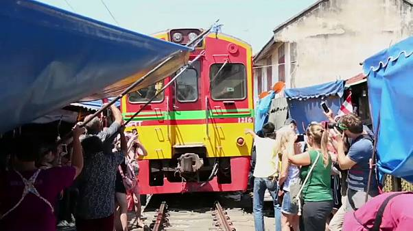 Market traders step aside as the train approaches while tourists step out