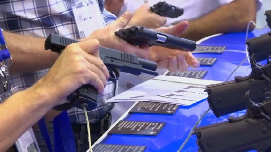أشخاص يختبرون مسدسات في معرض للدفاع والأمن في ريو دي جانيرو