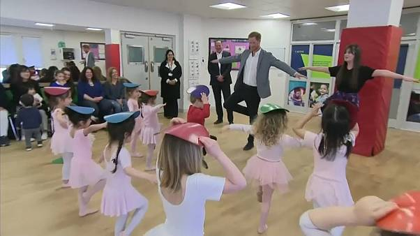 Dad-to-be Prince Harry observes a ballet class and makes a baby smile while visiting a YMCA