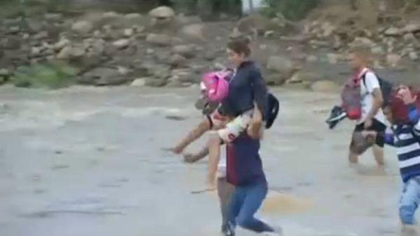 شاهد.. فنزويليون يجتازون نهرا يفصلهم عن كولومبيا هربا من أوضاع البلاد