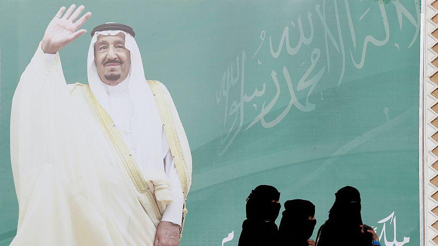 صورة عملاقة للملك سلمان وسيدات سعوديات ينظرن إلى الصورة