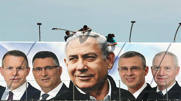 عمال يقومون بتنصيب لوحة دعائية لحزب نيتنياهو خلال الحملة الانتخابية للكنيست