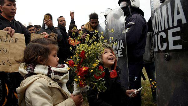 کودکان پناهجویان به پلیس ضدشورش گل هدیه میکنند- یونان- اردوگاه دیاواتا