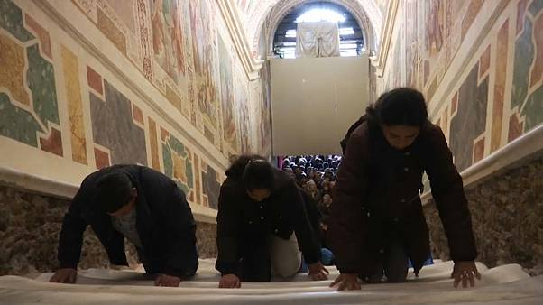 The faithful climb the Holy Stairs on their knees