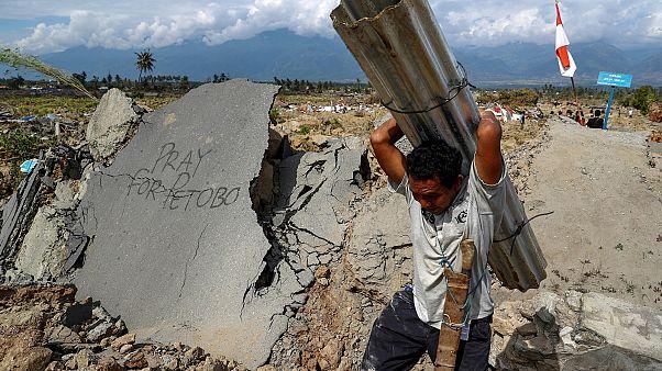 رجل إندونيسي يعمل بعد هزة أرضية ضربت البلاد منذ أيام