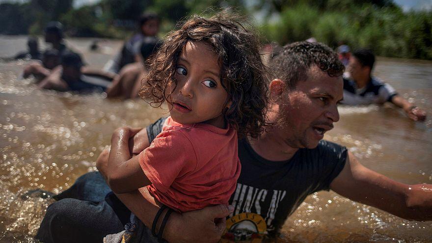 Ein Migrant aus Honduras hilft einem Kind über einen Fluss.