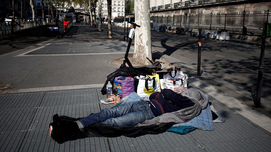 Paris'te bir evsiz metro havalandırmasının üzerinde uyuyor