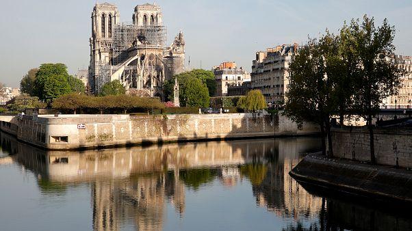 انعكاس صورة كاتدرائية نوتردام على مياه نهر السان في باريس بعد الحريق
