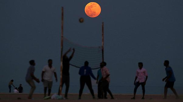 People play volleyball on the beach as the Pink Moon rises in the sky over