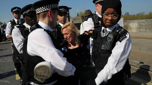 A climate change activist is detained during the London protest