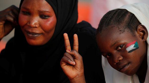 طفلة سودانية وعلى خدها رسمت علم السودان ترفع إشارة النصر رفقة أمها