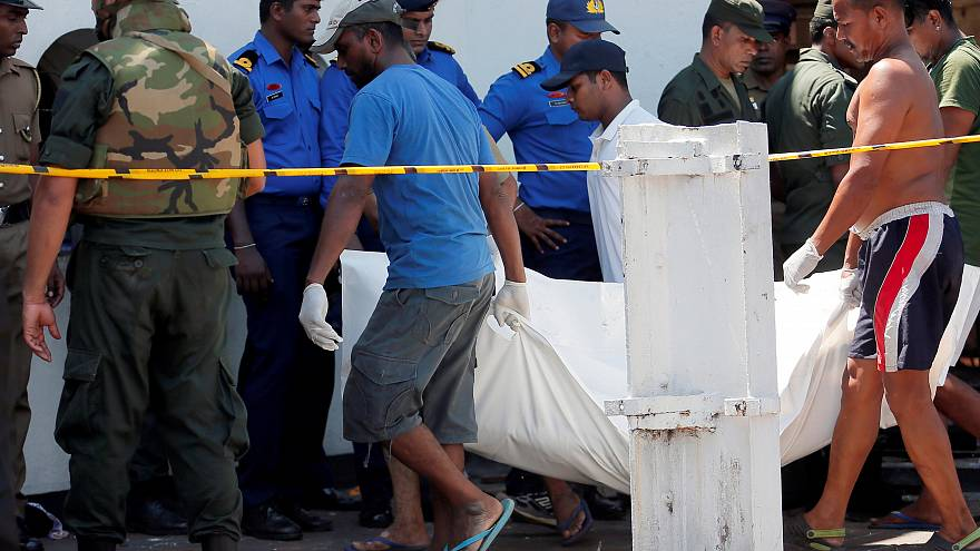 Men carry dead bodies towards ambulances in Colombo on April 21, 2019.