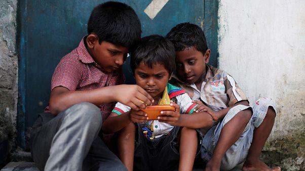 أطفال في إحدى الأحياء الفقيرة في نيودلهي يستغلون العاب الهاتف المحمول